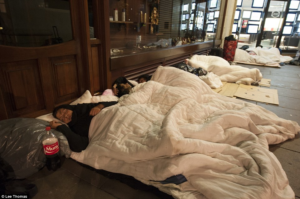 Women sleep in makeshift beds along shop fronts using blankets, cardboard boxes and plastic bags as bedding. They were among many rough sleepers 'processed' by authorities this morning