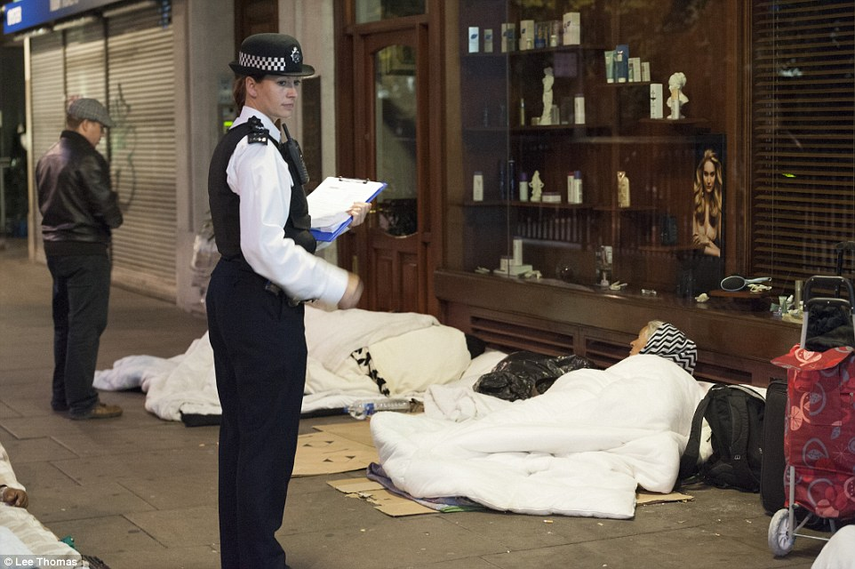 A female police officer stands guard as rough sleepers, camping out on makeshift beds next to a shop, are woken up and informed<br />  about the round-up operation